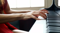 Woman in red dress playing piano (closeup on fingers) Stock Footage