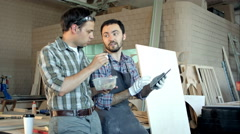 Two carpenters discussing work and one of them eating in workshop Stock Footage