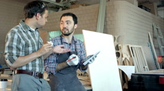 Two carpenters discussing ideas one of them eating and another is writing in Stock Footage