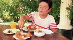 Child eating breakfast at the garden Stock Footage