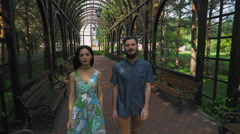 A young couple is on a path in the park, reviewed and smiles Stock Footage
