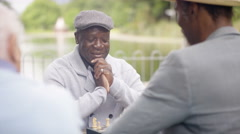 4K Portrait smiling senior man playing chess in the park with a friend Stock Footage