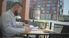 Businessman makes photo of document, in cafe, steadicam. Stock Footage