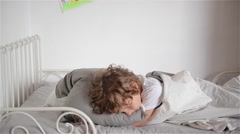 Overslept boy does not want to wake up, child falls out of bed Stock Footage