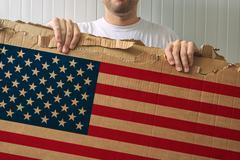 Man holding cardboard with USA flag printed Kuvituskuvat
