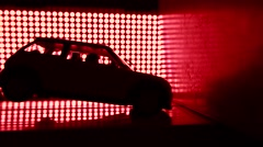 Toy car crashing into wall. Crash test lab concept. Red lights background, super - stock footage