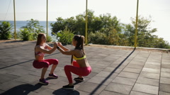 Sports girlfriend workout outdoor. They squat together. Stock Footage