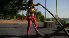 Sportswoman workout outdoor. Cross-training exercise with rope. Stock Footage