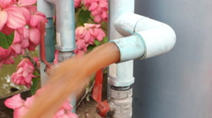 Dirty brown water running out of water filter in flower garden, Stock Footage