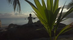 Girl Admires the Sunset Sitting Back on a Rock by the Sea. Slow Motion Stock Footage
