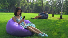 Young attractive brunette girl is sitting in a chair in the park and gaining a Stock Footage