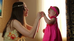 Mom puts little daughter rim on the hair. small child playing with his mother in Stock Footage