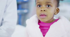 Female doctor uses a stethoscope to examine cute little girl in hospital Stock Footage