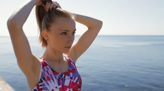 Sporty woman ties hair before training at sea background Stock Footage