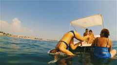 The girl in a bathing suit dives with a catamaran in the sea water Stock Footage