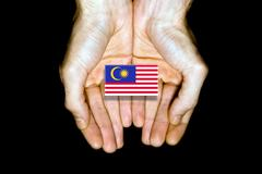 Flag of Malaysia in hands on black background Stock Photos