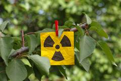 Radiation warning sign hanging on a tree Stock Photos