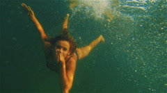 Girl in a bathing suit dives into the sea with a closed nose. She looks at the Stock Footage