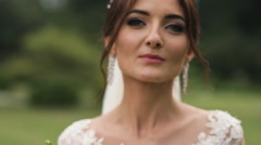 Portrait of a bride in wedding dress with flowers in a sunny park - stock footage