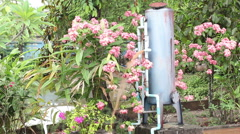 Dirty brown water running out of water filter in flower garden Stock Footage