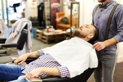 Barber shaving another man's beard in a barbershop Stock Photos