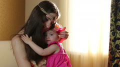Beautiful happy mother hugging baby girl with love. Mom plays with her daughter Stock Footage