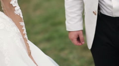 Wedding couple holding hands on green background shot in slow motion Stock Footage
