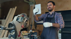 The carpenter makes selfie on tablet in the workshop near electric saw Stock Footage