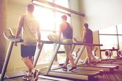 Men exercising on treadmill in gym Stock Photos