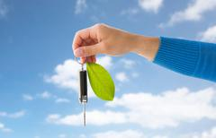 close up of hand holding car key with green leaf - stock photo