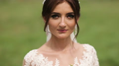 Portrait of a bride in wedding dress with flowers in a sunny park Stock Footage