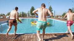Guy splashed females while sunbathing when jumped in pool. 20s. Super 1080p Slow Stock Footage