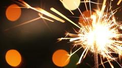 Burning sparkler on background blinking blurred garland Stock Footage