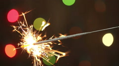 Burning sparkler on background blinking blurred garland Stock Footage