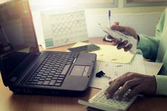 Expenses calculation by a man on office desk Stock Photos