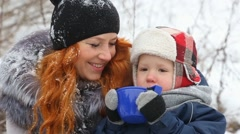 Mother and baby drink hot tea on winter picnic Stock Footage