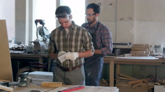 Two carpenters working with wooden planck and electric planer in workshop Stock Footage