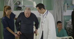 An attractive and caring young doctor and nurse help an elderly male Stock Footage