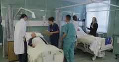 Doctors and nurses on a UK hospital ward are busy taking care of two elderly Stock Footage