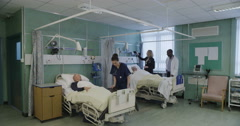 UK hospital ward. One male and one female nurse are looking after an elderly Stock Footage