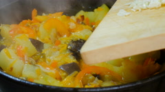 Garlic is added to the vegetable stew, stirred with a wooden spoon. Stock Footage
