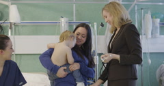 Very cute little boy sits on his mother's lap in hospital Stock Footage