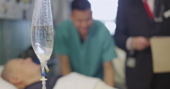 Close up of an IV drip at an elderly patients bedside. Stock Footage