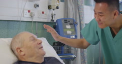 A male nurse attends to an elderly male patient as a doctor Stock Footage