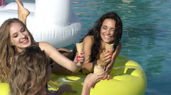 Two girls of swimsuit floating in the pool float. 20s. 4k Slow Motion Stock Footage