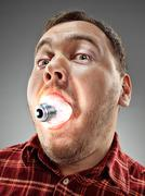 Caucasian man with bulb in his mouth on gray background Stock Photos