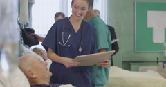 One male and one female nurse attend to an elderly male patient Stock Footage