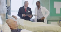 An elderly patient rests in bed as a doctor and consultant specialist discuss Stock Footage