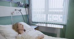 A female hospital patient is attended to by a male nurse Stock Footage