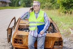 Inspector talking on smart phone near burned down car wreck Stock Photos